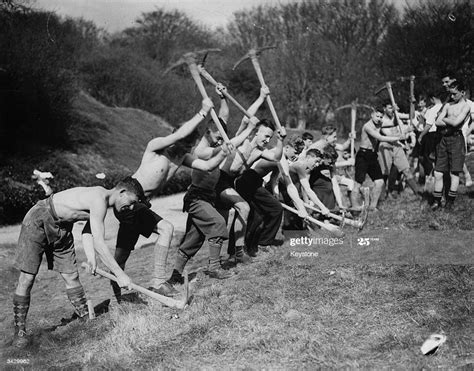 Stripped to the waist, schoolboys at camp in Dorset wield